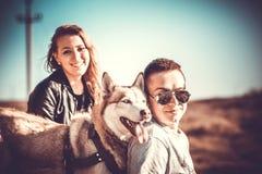 Les jolis couples reposent extérieur dans la forêt avec le chien de traîneau Photo stock