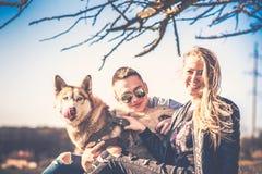 Les jolis couples reposent extérieur dans la forêt avec le chien de traîneau Image libre de droits
