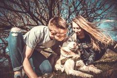 Les jolis couples reposent extérieur dans la forêt avec le chien de traîneau Photos libres de droits