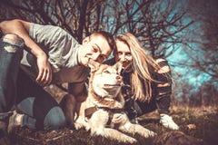Les jolis couples reposent extérieur dans la forêt avec le chien de traîneau Photos stock