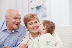 Les jolis grands-parents prennent soin d'enfant Images stock