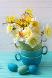 Les jonquilles jaunes de ressort fleurit en vase et oeufs de pâques Image libre de droits