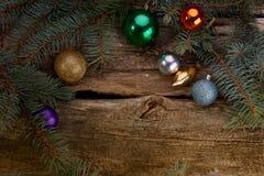Les jouets de Noël et les branches de l'arbre ont allumé la bougie photo stock