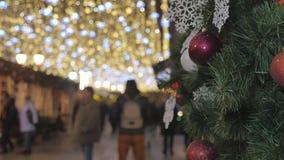 Les jouets rouges de Noël accrochent sur les branches du sapin Décoration de fête de la ville banque de vidéos