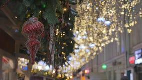 Les jouets rouges de Noël accrochent sur les branches du sapin Décoration de fête de la ville clips vidéos