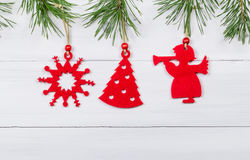 Les jouets rouges sur le pin s'embranche sur le fond en bois Photographie stock libre de droits