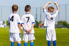 Les joueurs d'équipe de sport de la jeunesse soutiennent des équipiers sur le competi de sports photographie stock libre de droits