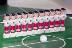 Les joueurs de football de jouet se tiennent dans le domaine dans une rangée et une boule au centre Photos stock