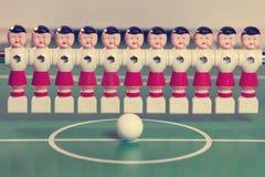 Les joueurs de football de jouet se tiennent dans le domaine dans une rangée et une boule au centre, rétro effet Photos stock