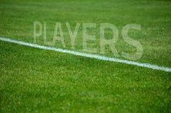 Les joueurs de football textotent sur l'herbe avec la ruelle blanche Photographie stock