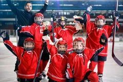 Les joueurs heureux de garçons team le trophée de gagnant de hockey sur glace image libre de droits