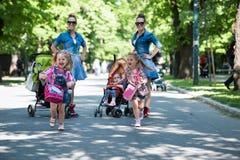 Les jumeaux enfantent avec des enfants en parc de ville Images libres de droits