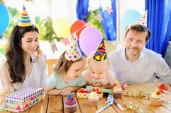 Les jumeaux mignons de petits enfants et leurs les parents ayant l'amusement et célèbrent la fête d'anniversaire avec la décorati Images libres de droits