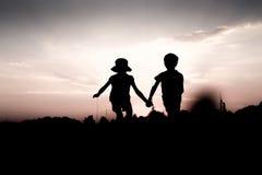 Les jumeaux sautent outre d'une colline tenant des mains au coucher du soleil Image libre de droits