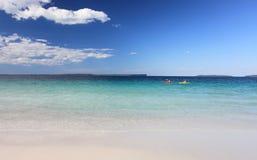 Les Kayakers apprécient la plage clair comme de l'eau de roche d'Australien des eaux images stock