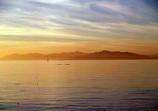 les kayaks de nuages silhouettent l'eau Images stock