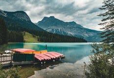 Les kayaks rouges sèchent à l'envers Emerald Lake dans le Canadien les Rocheuses avec des montagnes et des arbres et refelction C images libres de droits