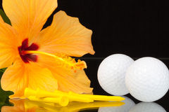 Les ketmies oranges fleurissent et les équipements de golf sur la table en verre Image stock