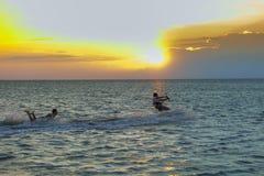 Les kitters professionnels fait un tour difficile contre le contexte d'un beau coucher du soleil images libres de droits