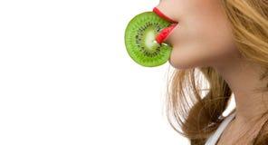 Les lèvres rouges de Gril mordant une tranche de kiwy Photos stock
