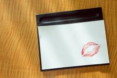 Les lèvres rouges embrassent le message sexy de matin de note vide blanche sur la table Photos libres de droits