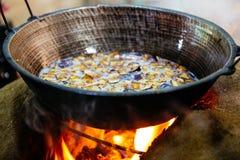 Les légumes étant faits frire au-dessus d'un fourneau mis le feu par bois ont fait hors de la boue a photographie stock