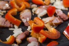 Les légumes coupés poivrent, oignon, et jambon de porc pendant faire frire Image stock