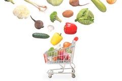 Les légumes d'isolement tombent dans le chariot du marché Image libre de droits