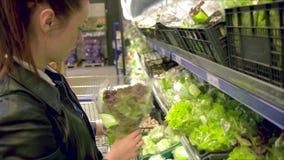 Les légumes de achat et les fruits de belles femmes dans le supermarché, brune choisissent la tomate et le poivre, salade fraîche banque de vidéos