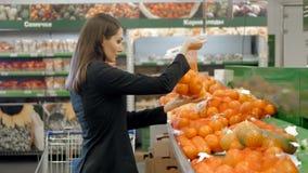 Les légumes de achat et les fruits de belles femmes dans le supermarché, brune choisissent la tomate et le poivre, salade fraîche Photographie stock libre de droits