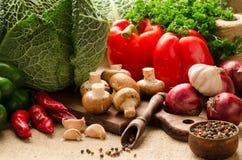 Les légumes, les champignons et les épices sur une cuisine embarquent sur renvoyer Photos stock