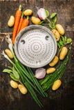 Les légumes organiques frais de jardin autour de la passoire vide roulent sur le fond en bois rustique foncé Photo stock