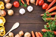 Les légumes se mélangent sur la table à la cuillère en bois Image libre de droits