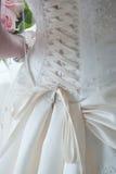 Les lacets desserrent en fonction de la robe de mariage Photographie stock libre de droits