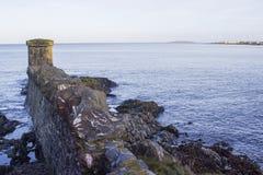 Les lais rocheux et les fortifications établies en pierre de reproduction au village de bord de la mer de Groomsport dans le comp Images stock