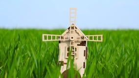 Les lames de moulin tournent dans le vent Un petit moulin décoratif se tient dans un domaine d'herbe verte banque de vidéos