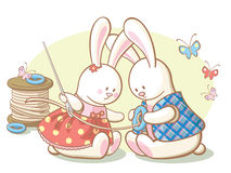 Les lapins cousent un bouton sur la jupe Photo libre de droits