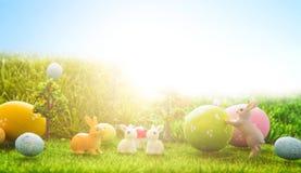 Les lapins de Pâques joue avec des oeufs de pâques sur l'herbe verte Image stock