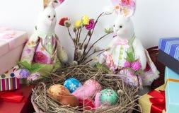 Les lapins regardent le panier avec les oeufs colorés pour Pâques image libre de droits