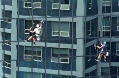 Les laveurs de vitres travaille au bâtiment ayant beaucoup d'étages Image stock
