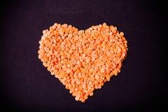 Les lentilles oranges à un coeur forment sur un fond noir toned images libres de droits