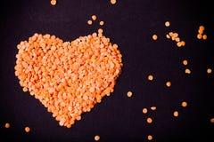 Les lentilles oranges à un coeur forment sur un fond noir toned photographie stock