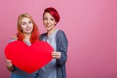 Les lesbiennes tiennent un coeur rouge au niveau de sein du côté gauche sur un fond rose Photo stock