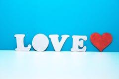 Les lettres AIMENT et coeur rouge de carton sur l'étagère blanche Photo stock