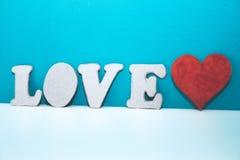 Les lettres AIMENT et coeur rouge de carton sur l'étagère blanche Images libres de droits