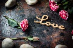 Les lettres AIMENT sur le fond rustique - concept du jour de Valentines Photographie stock libre de droits