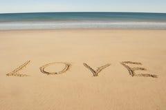 Les lettres d'amour écrites en sable sur l'océan échouent Photographie stock libre de droits