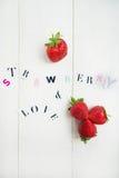 Les lettres de fraise et d'amour ont coupé de la magazine Photos stock