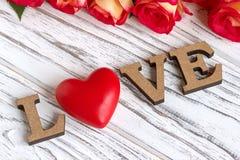 Les lettres en bois expriment AMOUR et fleur de rose de rose sur le fond en bois blanc Photo stock