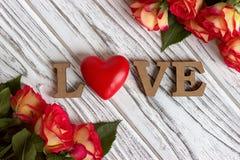 Les lettres en bois expriment AMOUR et fleur de rose de rose sur le fond en bois blanc Image stock